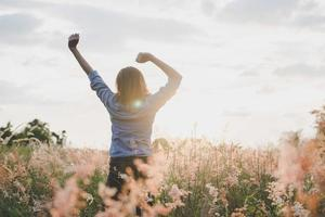 Young beautiful woman stretches her arms in the air in a field photo