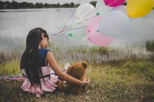 Little girl with a teddy bear and balloons on meadow field photo