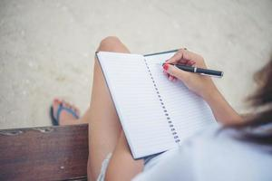 Beautiful young woman on a swing writing on her notepad photo
