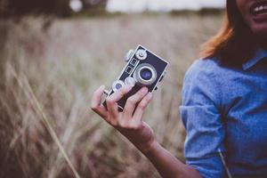 Feliz joven inconformista con cámara vintage en el campo