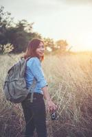 Young hipster woman backpacker with a vintage camera standing in a field photo
