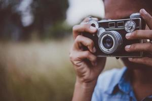 Young hipster woman takes a photo by a vintage camera