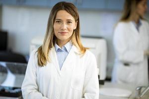 Investigadora en bata de laboratorio blanca de pie en el laboratorio biomédico foto