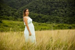 Young pregnant woman relaxing outside in nature photo