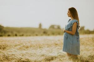 Young pregnant woman in blue dress relaxing outside in nature photo