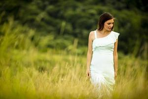 Young pregnant woman relaxing outside in nature