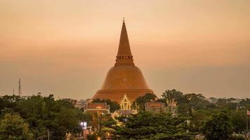Annual event of Phra Pathom Chedi, people climb up the pagoda to go up to collect the bells. Timelapse the skies changed in the evening.