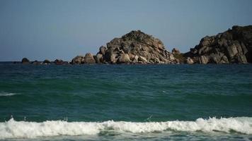 Zeitlupe von Wellen an einem Strand mit Felsen