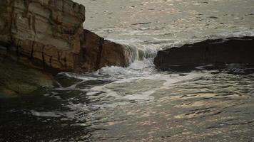fondo natural con rocas y olas. camara lenta. video
