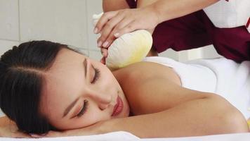 Masajeando a una mujer asiática feliz en el salón de spa
