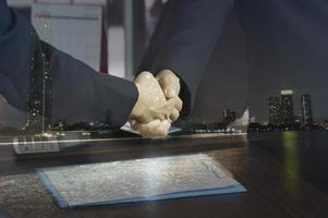 Double exposure businessman shaking hands photo