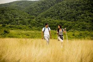 Pareja sonriente caminando con mochilas sobre colinas verdes