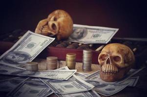 Dos cráneos con dinero y monedas sobre fondo oscuro foto