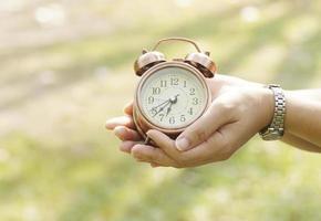 Hand holding alarm clock on green background photo