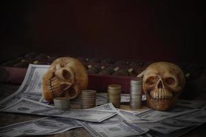 dos cráneos con dinero sobre fondo oscuro foto