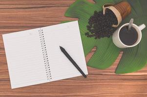 Cuaderno y tazas de café en el escritorio. foto
