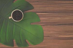 Coffee mug and a leaf on the desk