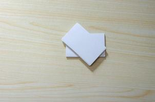 A blank paper mockup for business cards on a wooden table