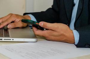Un empresario con un teléfono inteligente móvil y una computadora portátil en una mesa buscando en Internet foto