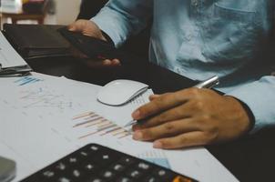 un empresario sosteniendo un teléfono móvil y un bolígrafo mirando documentos financieros en un escritorio foto