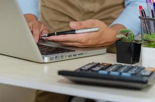 un empresario que usa una computadora para encontrar información mientras sostiene un bolígrafo foto