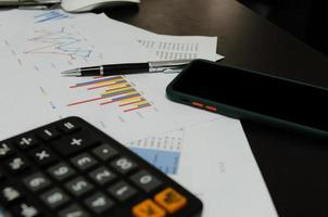 A mobile phone next to business documents, graphs, calculator, and pen