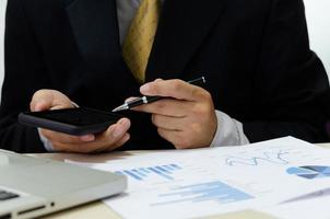 Businessman hand holding a cell phone and pen on the desk have business documents, graphs, and financial reports