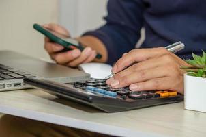Un empresario con una calculadora sosteniendo un bolígrafo y un teléfono móvil en un escritorio con una computadora portátil trabajando desde casa foto