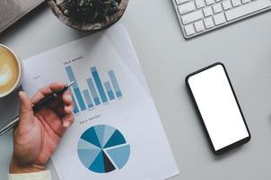 La mano de un hombre de negocios sosteniendo un bolígrafo sobre documentos comerciales, gráficos, informes e inversiones en una mesa gris, teléfono móvil, café y teclado de computadora foto