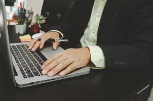 la mano de un hombre de negocios en una computadora y sosteniendo una pluma