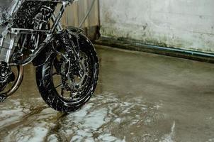 lavar una motocicleta en el taller de lavado de autos. lavado de coches de espuma sobre ruedas foto