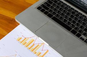 lugar de trabajo, análisis de gráficos con una computadora portátil en una mesa de madera