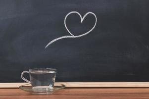 A glass of water and a heart shape on a blackboard