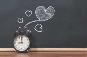 Alarm clock and a heart doodle on the blackboard