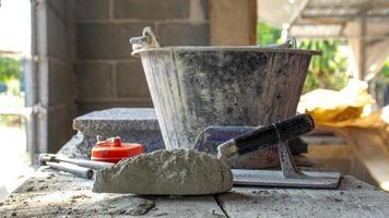 El cemento o el polvo de cemento y la paleta de construcción se colocan sobre una tabla de madera para la construcción.
