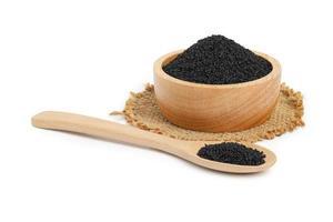 Sésamo negro en un tazón de madera y una cuchara de arpillera sobre fondo blanco. foto