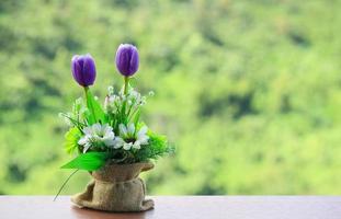 Flores de color púrpura en saco de arpillera sobre mesa de madera con fondo de naturaleza borrosa