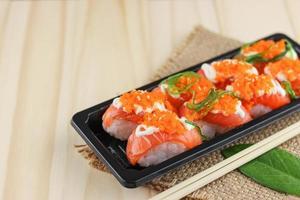 Sushi de salmón en placa negra y alfombrilla de arpillera con palillos sobre mesa de madera