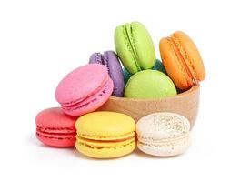 Colorful macarons in wooden bowl on white background