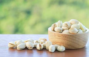 Pistachios in a wooden bowl and on wooden table with blurred nature background