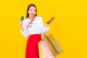 Young asian woman with credit card and shopping bag