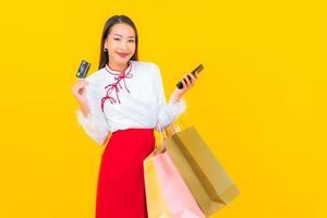 joven mujer asiática con tarjeta de crédito y bolsa de compras foto