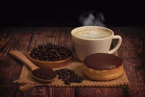 Donut, cup of steaming coffee with latte art, and coffee beans on burlap mat on a wooden table and black background