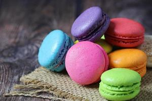 Colorful macarons on burlap mat on wooden table