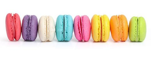 Line of colorful macarons on white background
