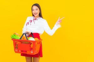 hermosa joven asiática con cesta de la compra