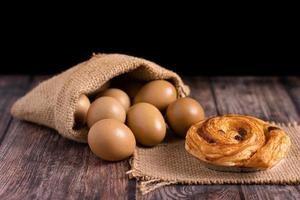 Croissant and eggs in a burlap sack on wooden table