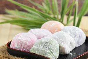 Colorful Japanese mochi dessert in black tray on wooden table