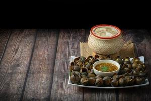 Cooked snail with thai spicy chili sauce on white plate and sticky rice basket on a wooden table