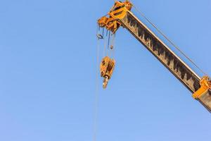 Yellow truck crane boom with hooks for lifting containers photo